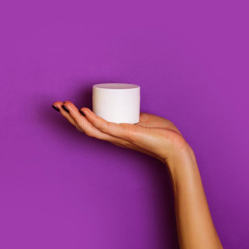 Female hands holding white cosmetic bottle on violet background. Banner. Skin care, pure beauty, body treatment concept. Square stock photography