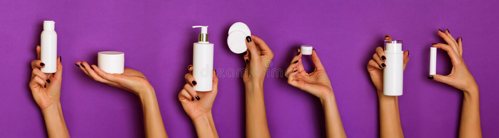 Female hands holding white cosmetics bottles - lotion, cream, serum on violet background. Banner. Skin care, pure beauty, body royalty free stock photography