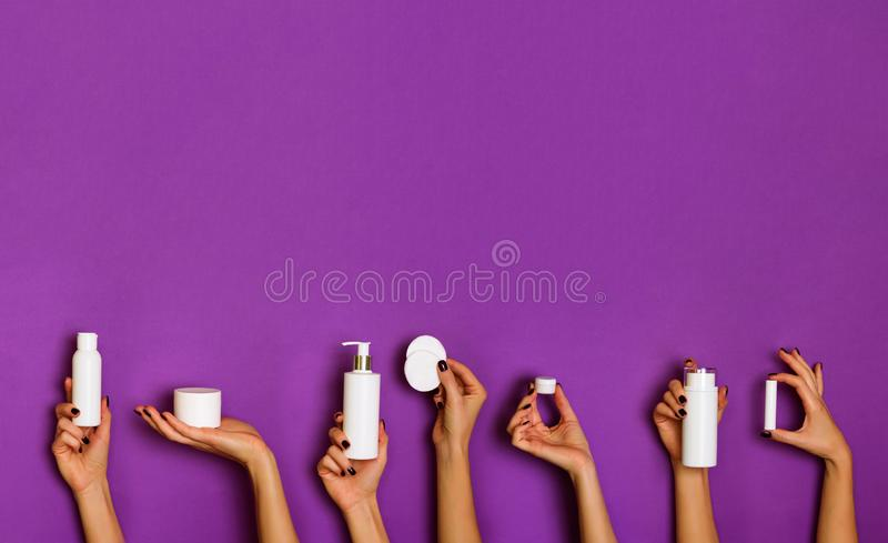 Female hands holding white cosmetics bottles - lotion, cream, serum on violet background. Square crop. Skin care, pure beauty, royalty free stock photos