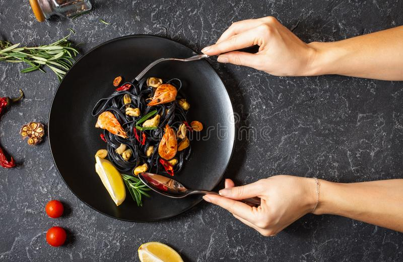 Female hands holds spoon and fork. Black spaghetti. Seafood pasta with mussels and prawns over stone background stock photography