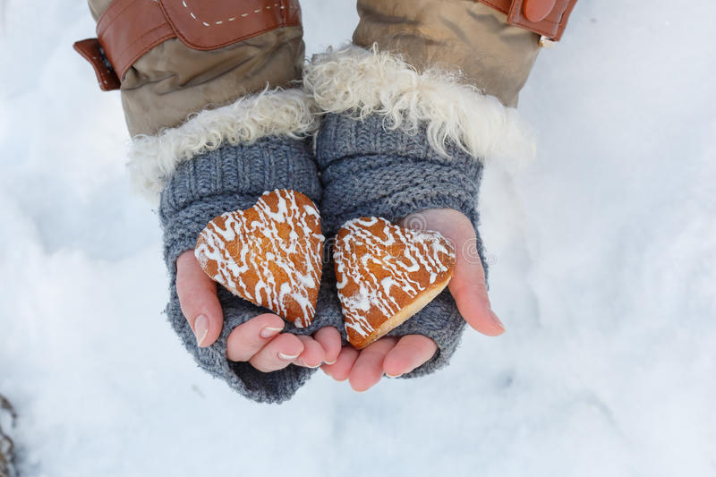 Female hands in knitted grey mittens hold beautiful heart shaped. Biscuit cookies with white icing at snow background. Focus on cookies. Top view royalty free stock image