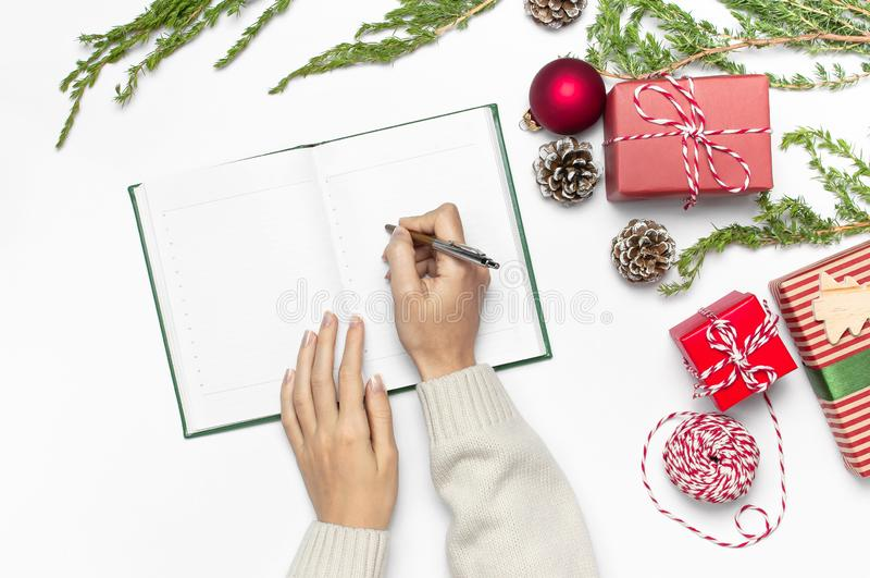 Female hands in knitted sweater are writing with pen in clean notebook plans for the new year, gift boxes, fir branches on white t royalty free stock photos