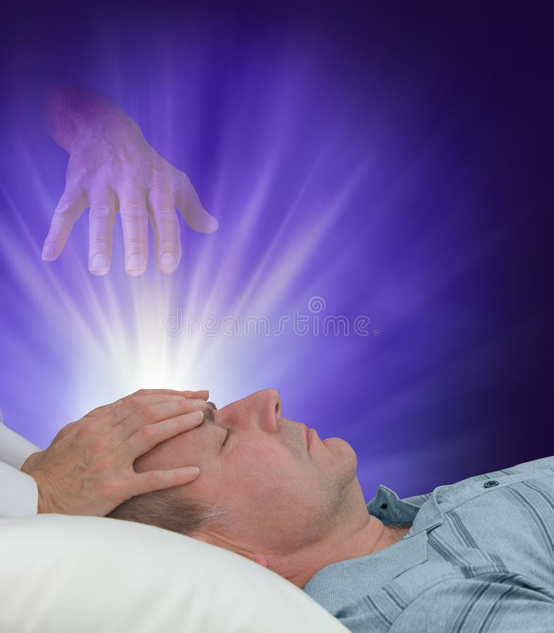 Receiving healing from the other side. Female hands laid gently on forehead of a man relaxing and an ethereal helping hand reaching down from spirit world stock image