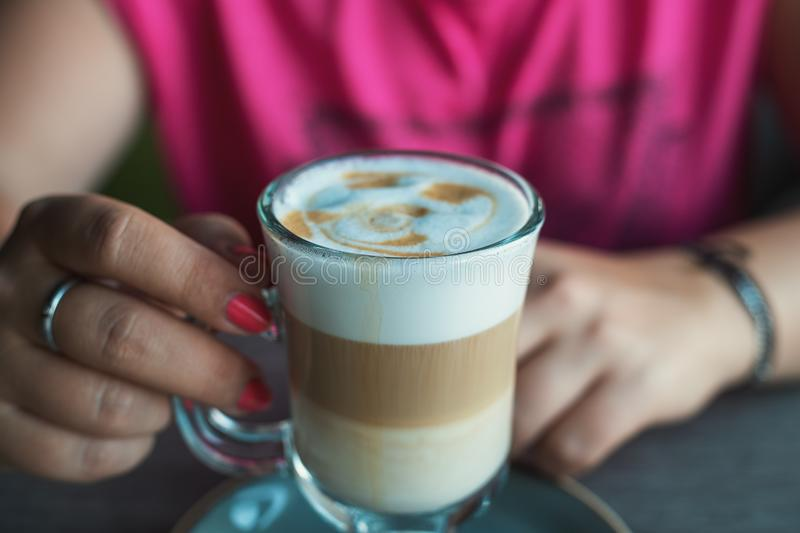 Female hands with latte coffee in cafe, close up stock photos