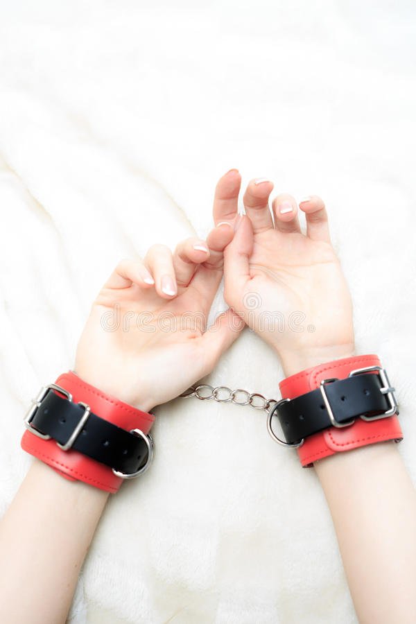 Female hands in leather handcuffs. on the royalty free stock photo