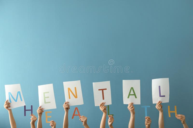Female hands with letters forming text MENTAL HEALTH on color background royalty free stock photo