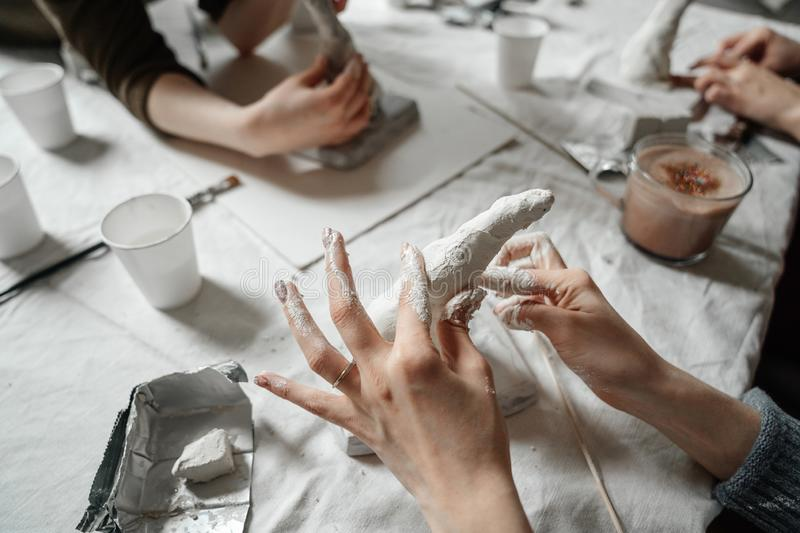 Female hands make plastic and plaster molds in class. Workshop and creative team work on the production royalty free stock photography