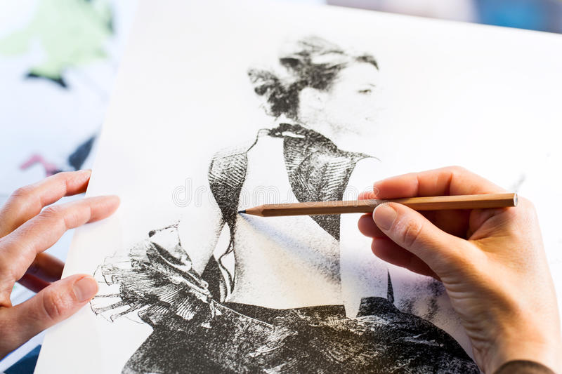 Female hands making fashion sketch. Extreme close up of female hands making fashion sketch royalty free stock images