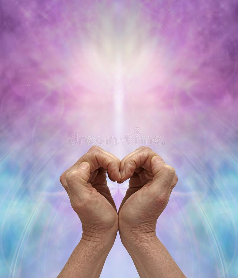 Meditate on heart healing energy. Female hands making a heart shape against a pink and blue energy formation background with copy space stock photography