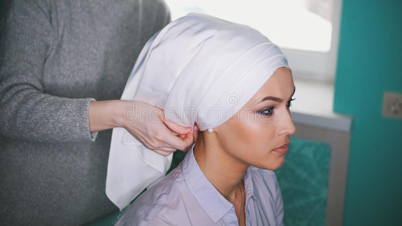 Female hands making islamic wedding headdress for the beautiful muslim bride royalty free stock photography