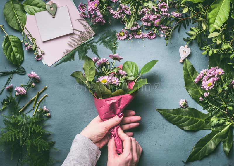 Female hands making lovely bouquet of pink flowers with wrapping paper on florist workspace stock images