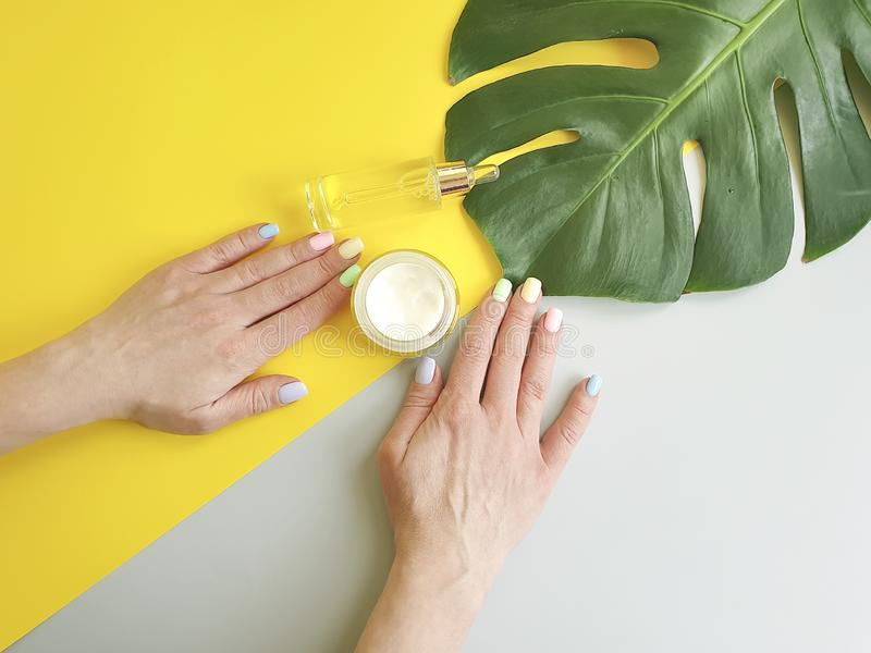 Female hands manicure, cosmetic hygiene essence creative cream summer , monstera leaf on a paper colored background royalty free stock photography