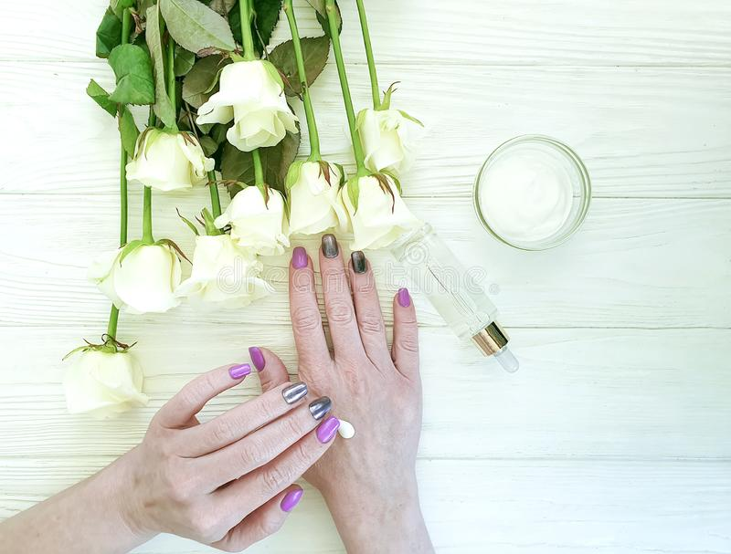 Female hands manicure , cream natura wellness l flower rose on a wooden background hygiene stock photography