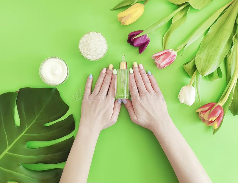Female hands manicure, essence creative moisturizer summer therapy cream cosmetic tulip on a colored background stock photos