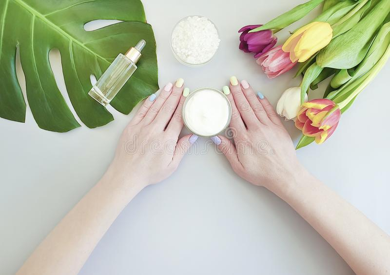 Female hands manicure, essence moisturizer summer therapy cream cosmetic tulip on a colored background royalty free stock photo