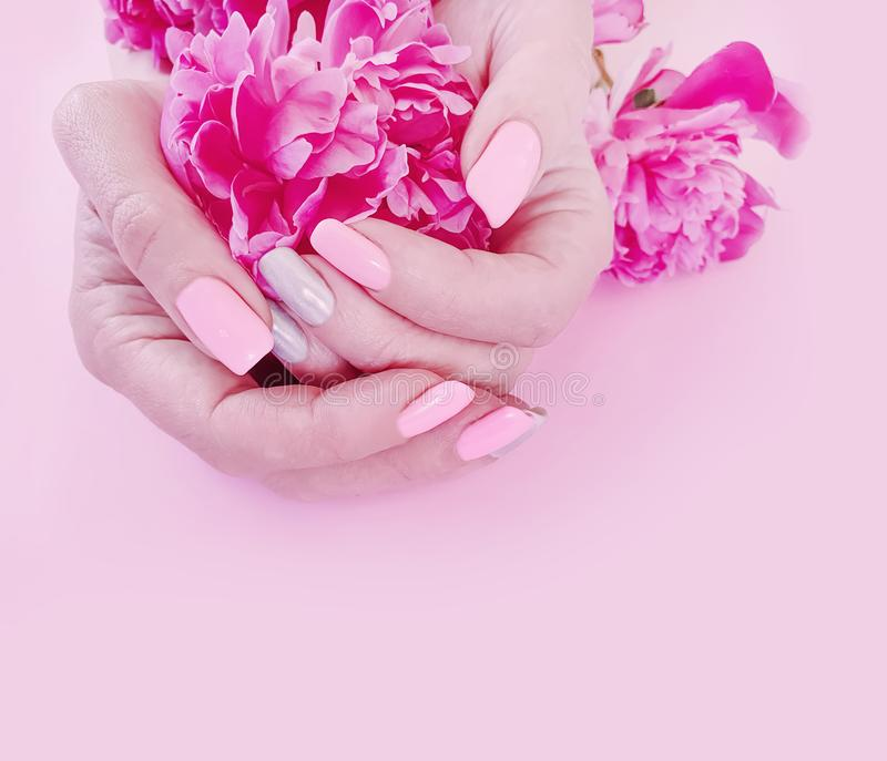 Female hands manicure style flower peony glamour on a pink background stock photos