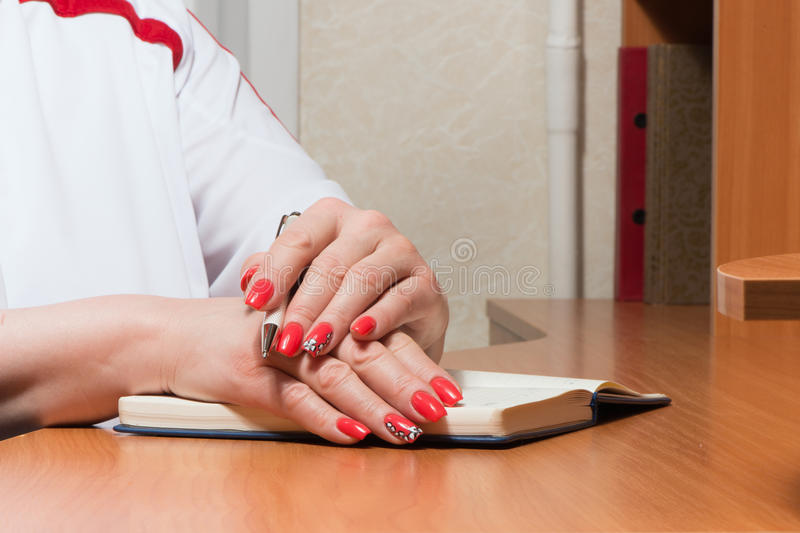 Female hands with manicure over pages of a notebook. Hold a pen stock photo