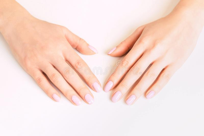 Female hands with manicure and pink pastel color polish. stock photo