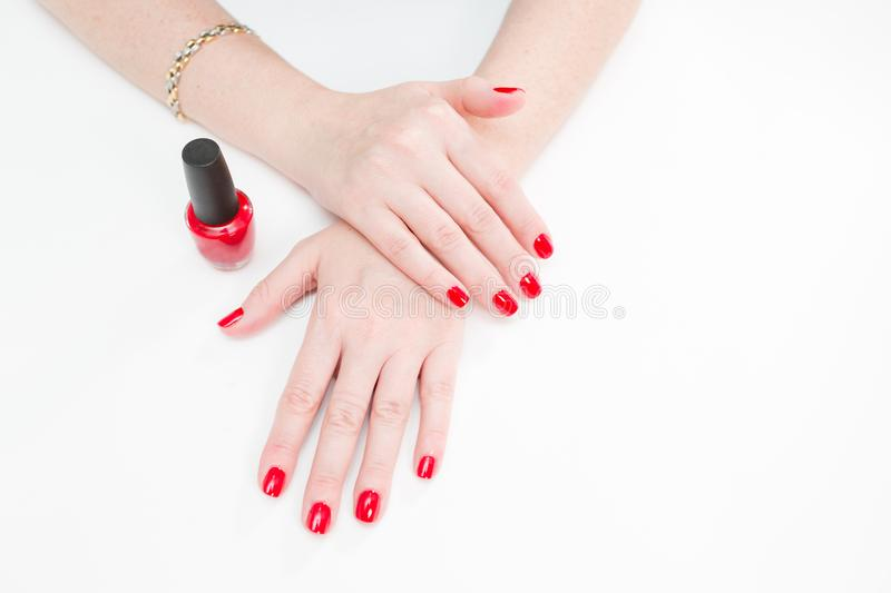 Female hands with manicure and red lacquer on a white table in the beauty salon. closeup of hand of a young woman. Female hands with manicure and red lacquer on royalty free stock image