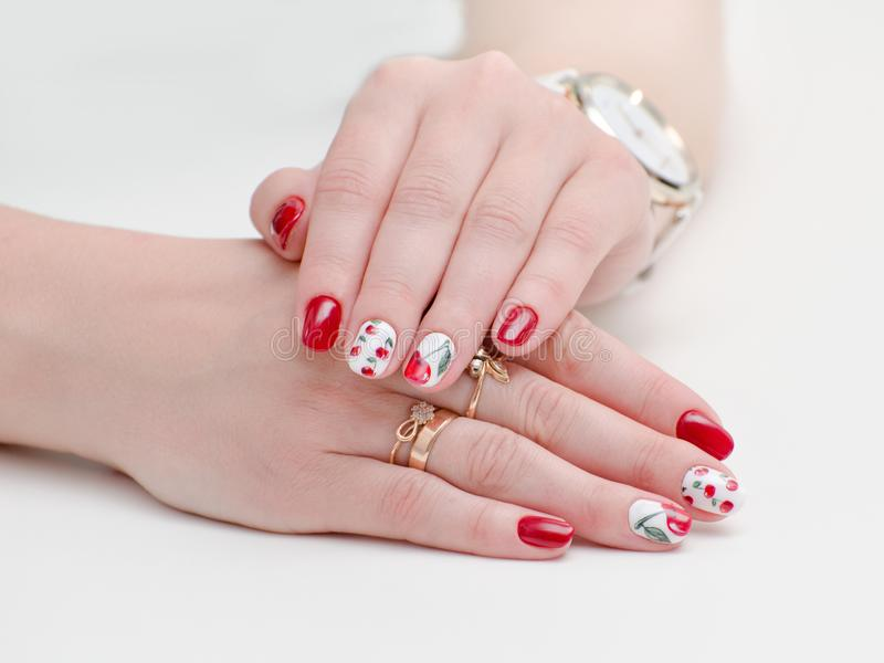 Female hands with manicure, red nail polish, drawing with cherries. White background. royalty free stock photos