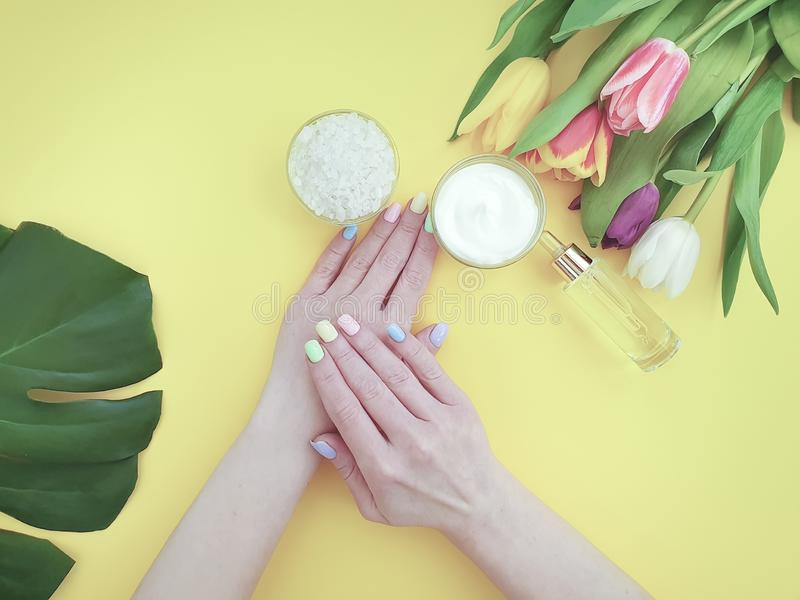 Female hands manicure, tulip flower  cosmetic hygiene essence creative cream summer , monstera leaf on a paper colored background royalty free stock image