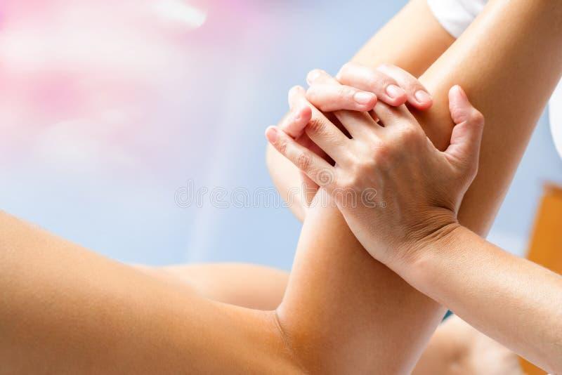 Female hands massaging calf muscle. Macro close up of osteopath massaging female calf muscle. Hands manipulating lower leg muscle royalty free stock photos