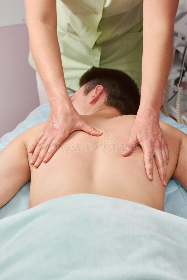 Female hands massaging male back. stock photos