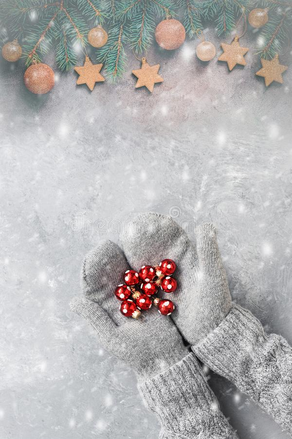 Female hands in mittens hold red Christmas balls, the border of the spruce branch is decorated with gold balls and stars. Top view stock images
