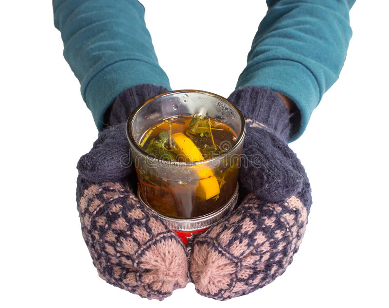 Female hands in mittens, holding an old glass with tea. stock photos