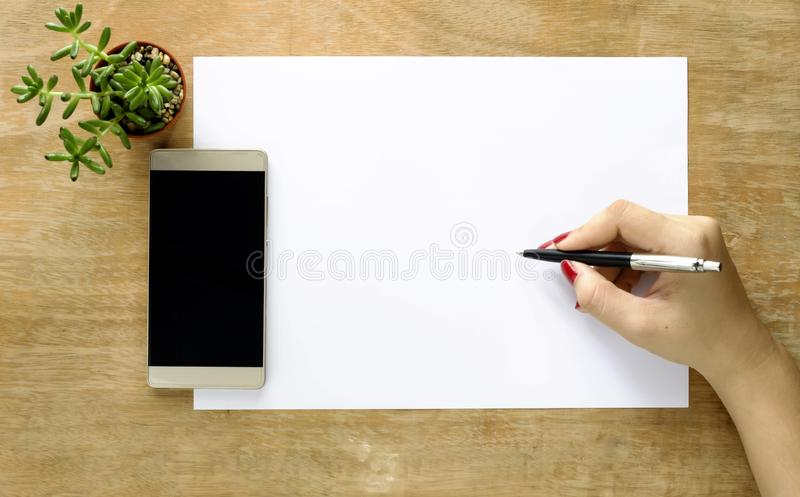 Female hands with a notebook and pen, phones and tree on table stock images