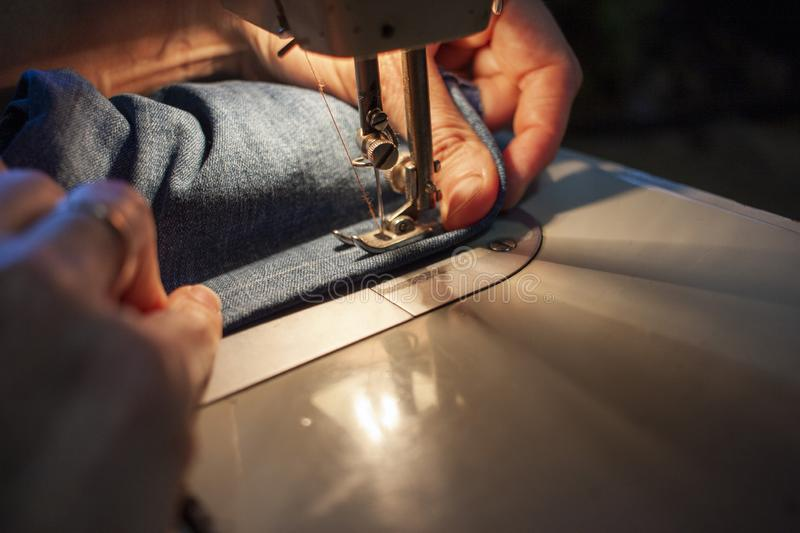 Female hands on an old sewing machine sew denim. Close-up royalty free stock image