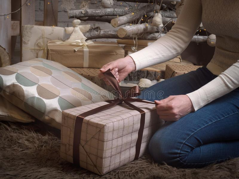 Female hands open a New Year`s gift. Gift box with brown ribbon, soft carpet and other gifts, jewelry and garland. royalty free stock photos