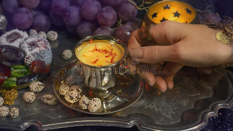 Female hands with oriental jewelery Pouring Tea into Cup. Traditional Moroccan Sweets. Cup of Saffron Masala milk Tea stock image