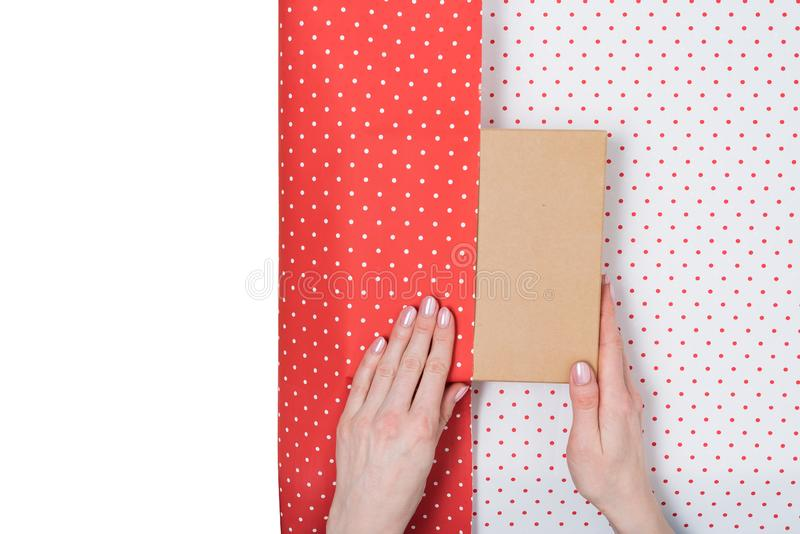 Female hands pack a gift in white-red polka-dot paper. White copy space. Top view stock photos