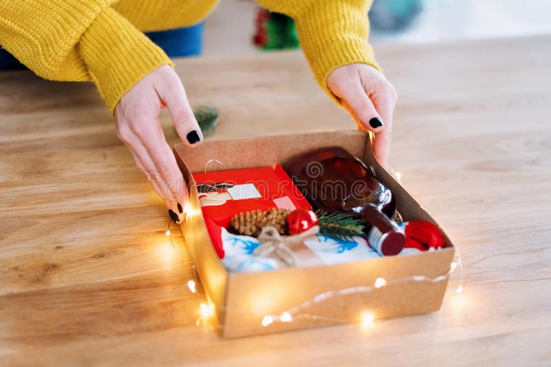 Female hands packing Christmas present on wooden table. Wrapping gifts at home. stock image