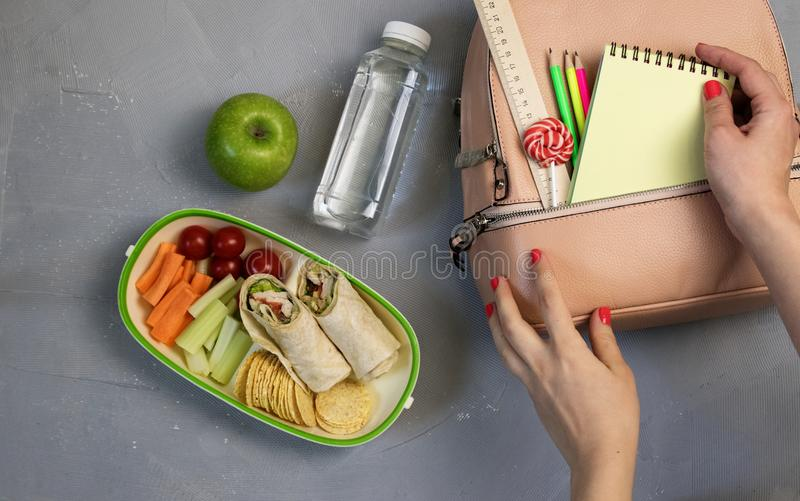 Female hands packing dinner in lunchbox on grey table royalty free stock photo