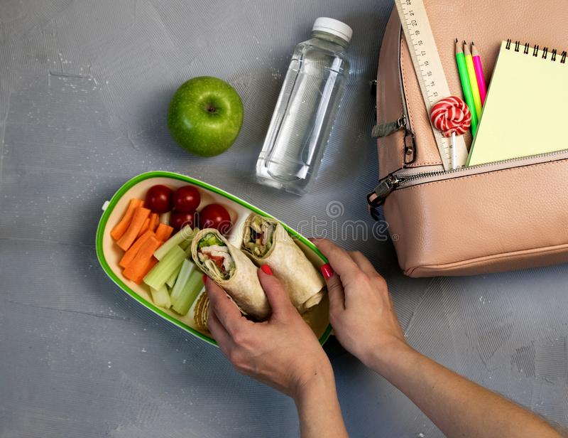 Female hands packing dinner in lunchbox on grey table royalty free stock image