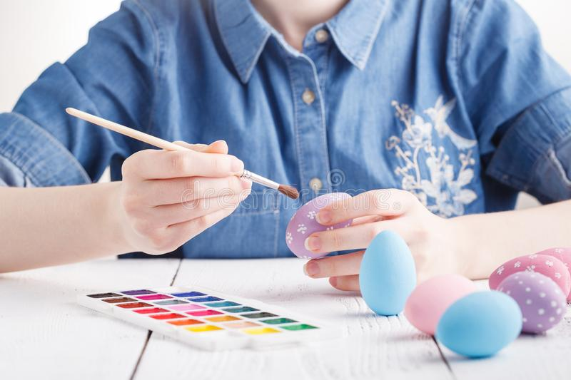 Female hands painting Easter eggs stock image