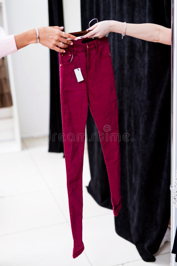 Female hands passing new women s jeans to a fitting booth in shopping mall.  royalty free stock photography