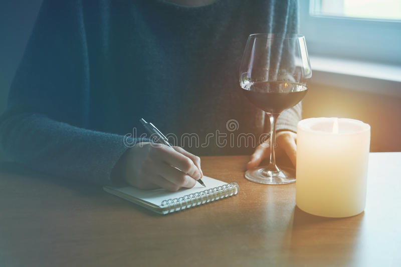 Female hands with pen and glass of wine writing. On notebook in candle light stock image