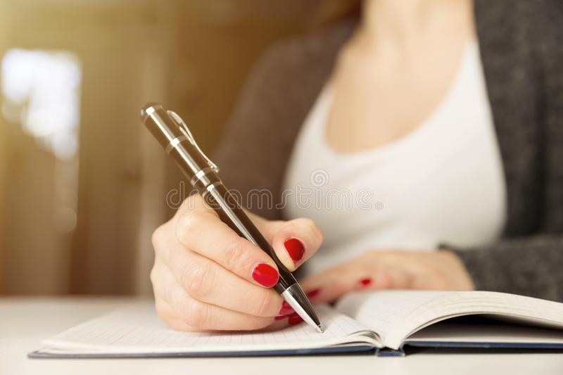 Female hands with pen writing on notebook. Diary, plans, journalist royalty free stock photo