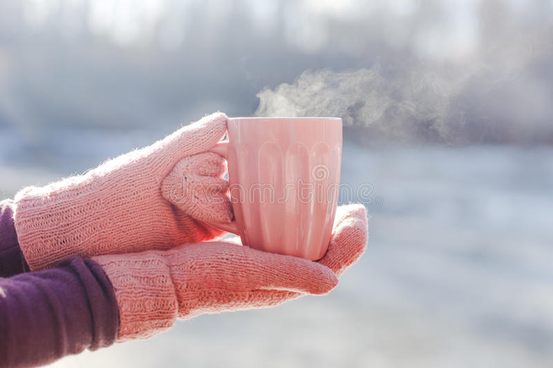Female hands in pink mittens holding cup with hot tea or coffee. Close up stock images