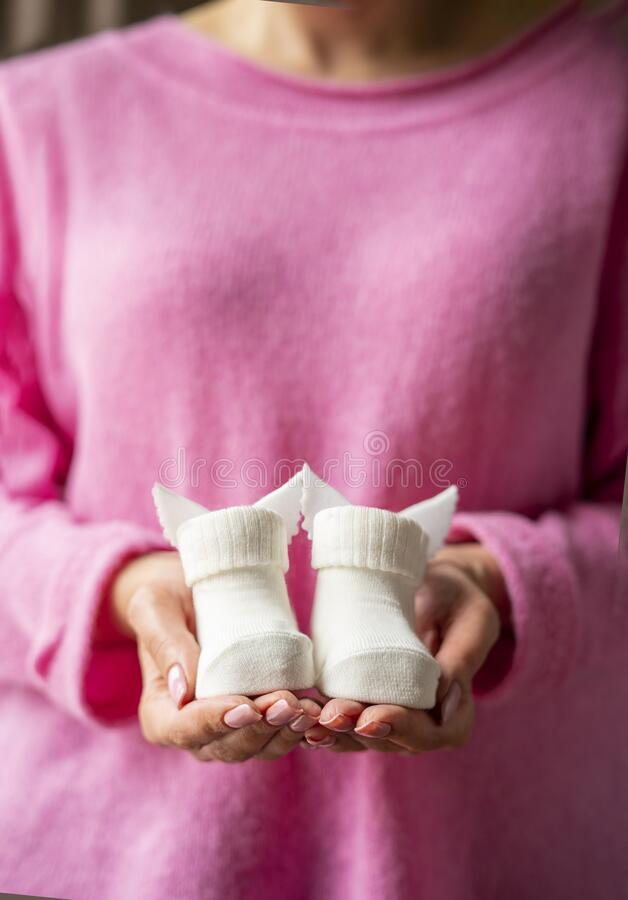 Female hands in pink sweater hold white booties royalty free stock photography