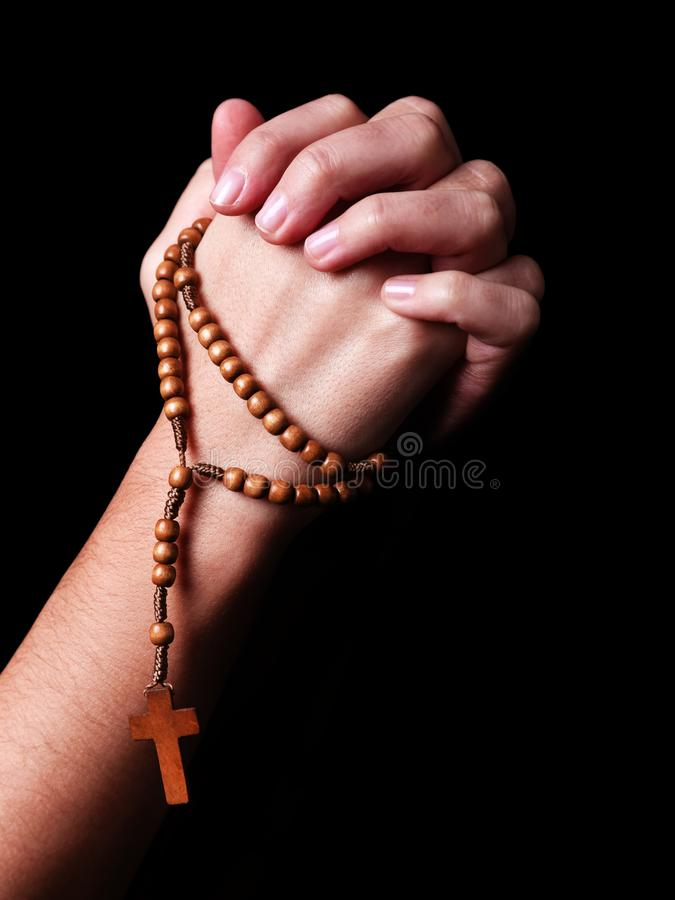 Female hands praying holding a beads rosary with a cross or Crucifix on black background stock photos