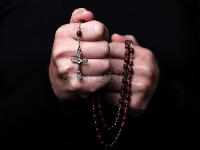 Female hands praying holding a rosary with Jesus Christ in the cross or Crucifix on black background. stock image