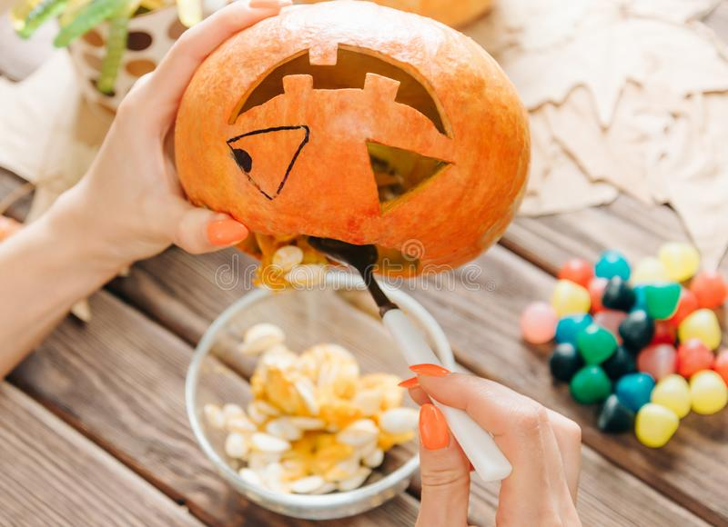 Female hands preparing jack-o-lantern pumpkin for Halloween. royalty free stock photo