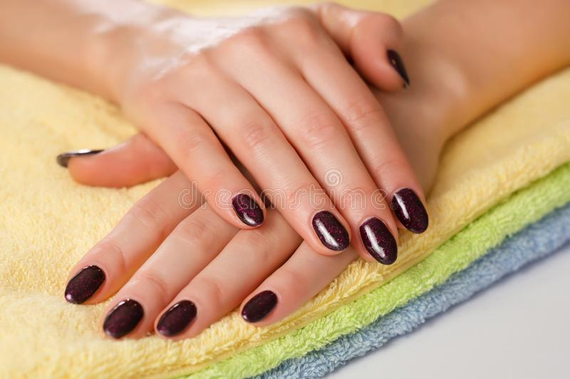 Female hands with purple nails art with tinsel on yellow, green and blue towels. Manicure and beauty concept. Close up, selective focus royalty free stock images