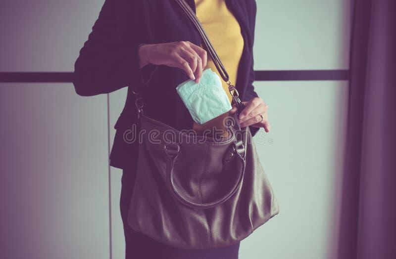 Woman hand putting sanitary napkins in handbag,White menstrual pad. Female hands putting sanitary napkins in handbag,White menstrual pad royalty free stock images