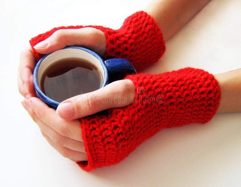 Female hands in red mittens are holding a cup of hot drink royalty free stock images