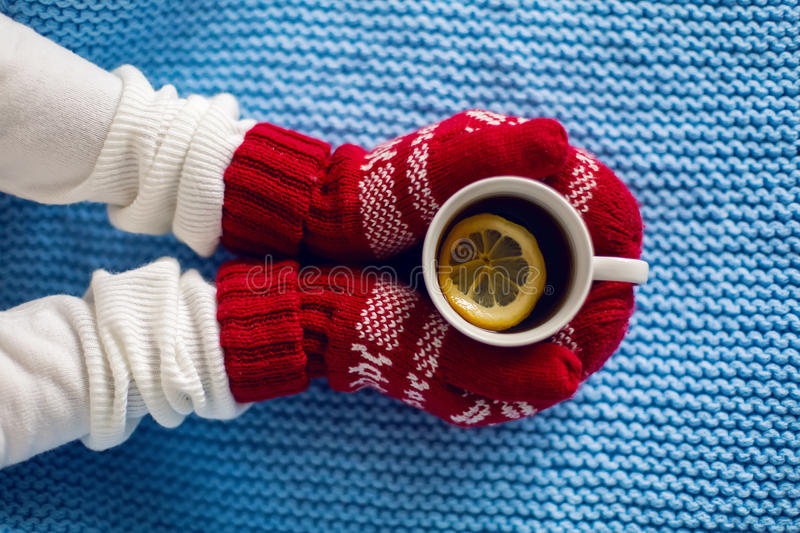 Female hands in red mittens holding a mug of tea stock photo